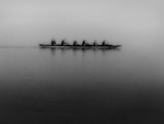 Men rowing a boat in the fog.