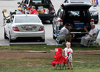 A young fan sets up a chair in a tailgating area across from the stadium during Saturday's NCAA Division I football game between the Ohio State Buckeyes and the Navy Midshipmen at M&T Bank Stadium in Baltimore on August 30, 2014. (Dispatch Photo by Barbara J. Perenic)