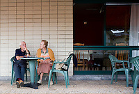 An older couple sit outside a bar. Sopelana beach and the Sopelmar housing bloc just outside of Bilbao, Spain.
