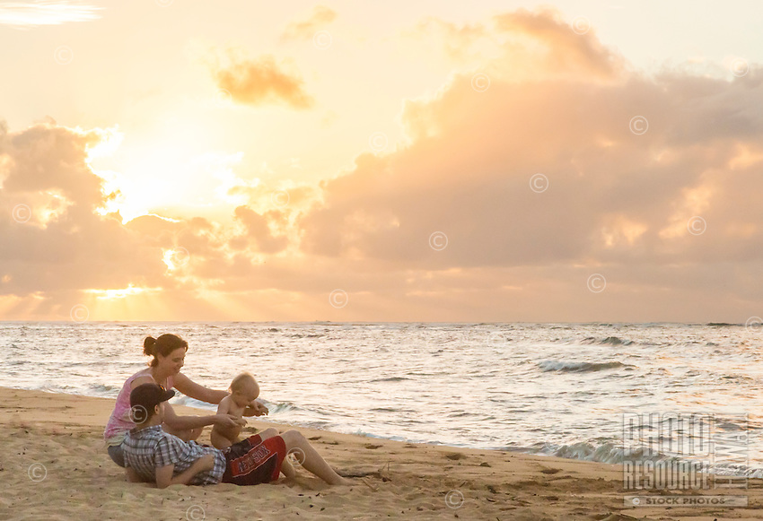 A family enjoys the beach at sunset, Waialua Beach, O'ahu.
