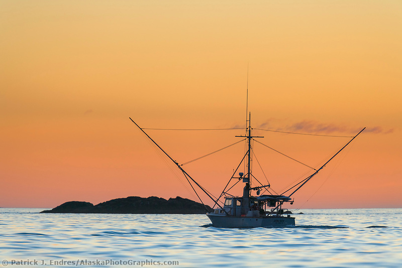 Commercial fishing trolling vessel in Sitka Sound at sunset in southeast Alaska.