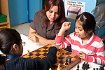 Afterschool chess program for elementary students graduates of Headstart program female teacher working with two girls