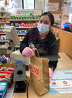 4//19/20-New York, New York City, during the time of the Coronavirus. The new face of shopping. The woman working behind the counter at CVS pharmacy is protected by  a face mask, gloves and plexiglass. I felt like I was buying radiated contraband rather than shampoo. I'm glad our essential workers are well protected but it's certainly a whole new world we're living in!