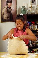 NATIVE-AMERICAN GIRL MAKING INDIAN FRYBREAD AT HOME. NATIVE-AMERICAN GIRL (8). OAKLAND CALIFORNIA.