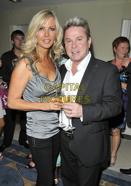 SUE MOXLEY & DAVID VAN DAY.At the Chelsea Summer Gala, Wyndham Grand Hotel, Chelsea Harbour, London, England, 23rd July 2010..half length grey gray silver top suit drink white shirt black trousers champagne .CAP/CAN.©Can Nguyen/Capital Pictures.