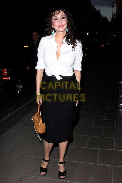 MARIE HELVIN .At the David Bailey Party, Claridge's hotel, London, England, UK,.May 11th 2010..full length white shirt black pencil skirt woven basket brown wicker tied  knotted ankle strap peep toe sandals hand in pocket .CAP/AH.©Adam Houghton/Capital Pictures.