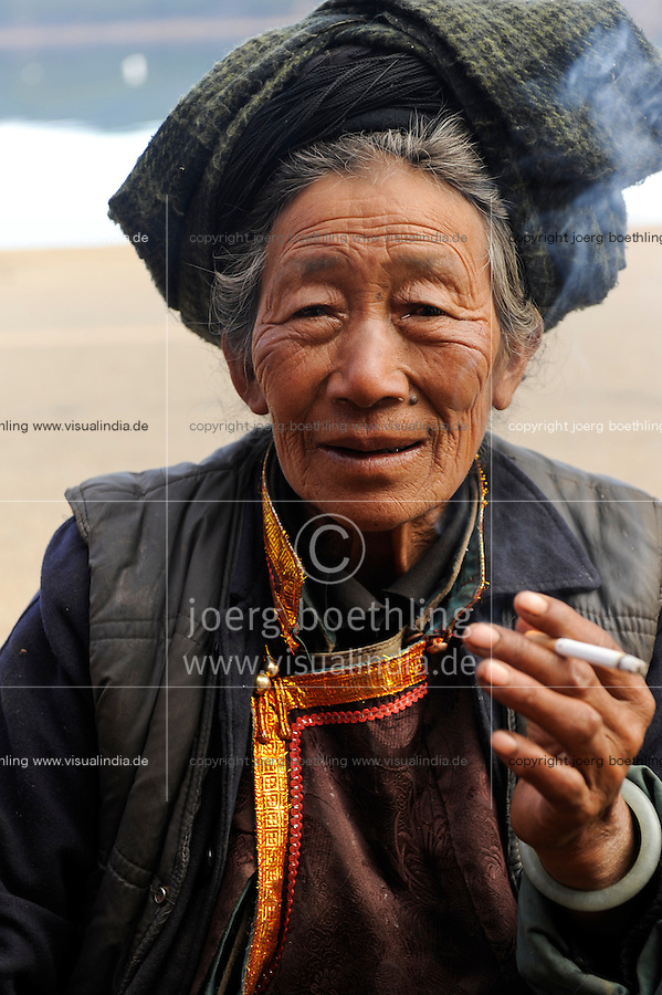 CHINA Yunnan Lugu Lake , Naxi woman, smoking, ethnic minority Naxi / CHINA Provinz Yunnan , ethnische Minderheit Naxi am Lugu See , rauchende Frau