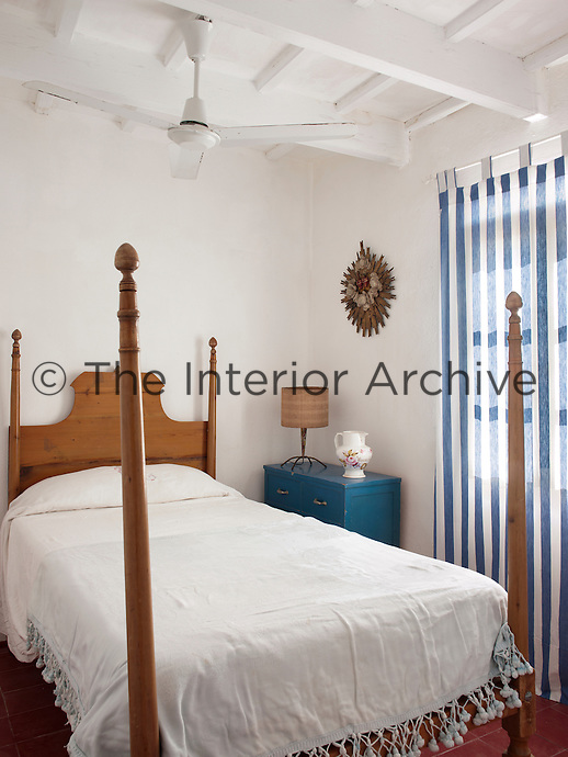 The small bedroom is furnished with a four-poster bed and has a fresh summery feel with its whitewashed walls and blue and white striped curtains