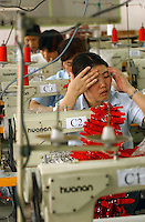 Workers on the production line of a factory in Zhouqing, Guangdong Province, China.The factory makes promotional gift items..06 May 2005