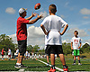 Joe Vito, head coach of Roosevelt varsity football, teaches catching technique during the Long Island Youth Football Player Academy at Cedar Creek Park in Seaford on Monday, July 11, 2016.