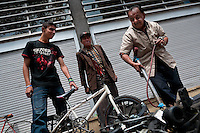 Colombian service men fix a BMX bike in an improvised bicycle repair shop on the street during the Car Free Day in Bogota, Colombia, 23 May 2010.