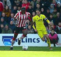 Lincoln City's John Akinde vies for possession with Cheltenham Town's Ben Tozer<br /> <br /> Photographer Andrew Vaughan/CameraSport<br /> <br /> The EFL Sky Bet League Two - Lincoln City v Cheltenham Town - Saturday 13th April 2019 - Sincil Bank - Lincoln<br /> <br /> World Copyright &copy; 2019 CameraSport. All rights reserved. 43 Linden Ave. Countesthorpe. Leicester. England. LE8 5PG - Tel: +44 (0) 116 277 4147 - admin@camerasport.com - www.camerasport.com