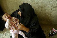 Zahra Jatea holds her granddaughter, 11 month old, Bakir, as she get medication from the doctor as both of her grandchildren are sick. Many of the infectious diseases are spread and caused by the poor water quality and overall sanitation problems.  Issues such as water, sanitation and utilities contiinues to be growing issue for the new government in Iraq.