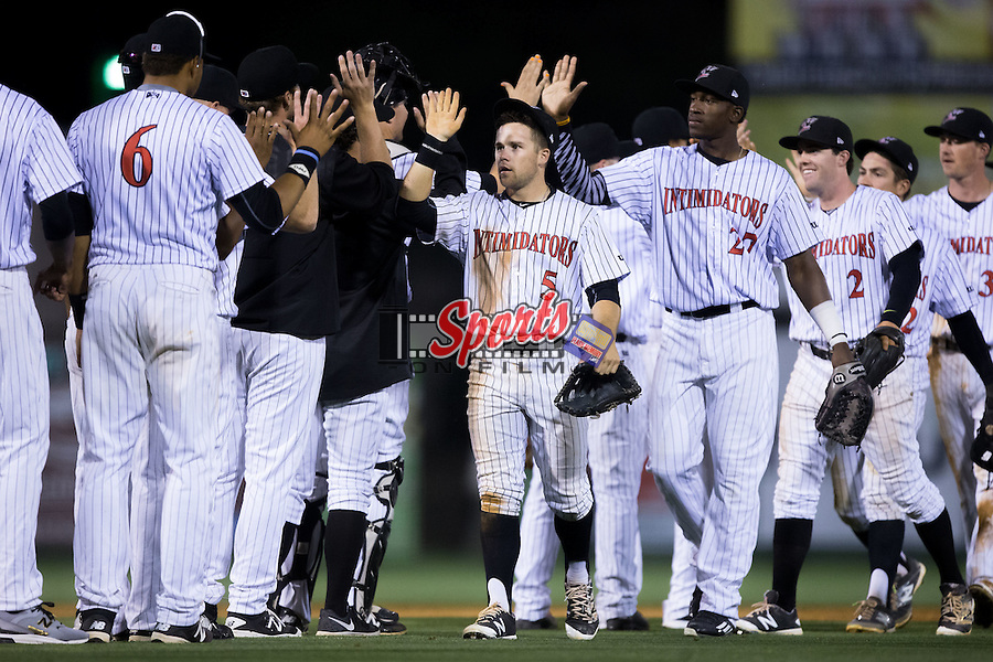 Tyler Sullivan (5) and Micker Adolfo (27) of the Kannapolis Intimidators high five teammates following their win over the Delmarva Shorebirds at Kannapolis Intimidators Stadium on April 21, 2016 in Kannapolis, North Carolina.  The Intimidators defeated the Shorebirds 9-3.  (Brian Westerholt/Four Seam Images)