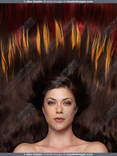 Beautiful woman with brown hair lying on colorful hair extensions in a shape of fire