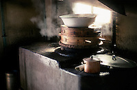 Traditional Chinese bamboo steaming pots, surmounted by a workaday enamel bowl, are used to cook lunch in a yurt resthouse near Lake Karakul on the Karakoram Highway.