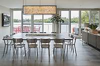 The open plan dining and living space provides ample space for the family to gather and the sliding glass doors lead straight to the terrace. The dining table which seats 10 is made of a bleach wood with bespoke aluminium legs. The contemporary chandelier light fitting is full of clear baubles which creates a stunning effect when lit.