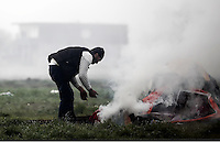 Pictured: A man starts a fire outside his tent Tuesday 08 March 2016<br /> Re: Heavy overnight rain has flooded the migrant camp at the Greek FYRO Macedonian border of Idomeni in Greece