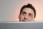 Smiling young man behind a laptop,<br />