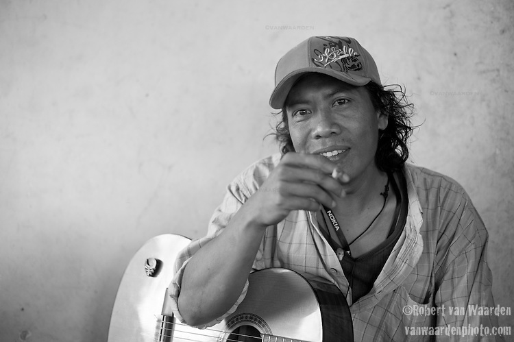 Portrait of Indonesia man with guitar and cigarette, Lombok, Indonesia.