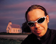 A priest in sunglasses stands in front of his church