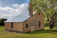 The old Crabapple School outsde of Fredericksburg Texas. <br /> Farmer Mathias Schmidt donated the land for a Crabapple school, earning the privilege by running a footrace with neighbor Crockett Riley who had also offered to donate land.Area families built the native limestone structure with their own labor. The 1878 school had a single classroom, with an adjoining room for the teacher living quarters. An outer staircase led to a second story storage space. An additional room was added later.<br /> <br /> The original schoolhouse also served as a post office from 1887-1910. The first postmaster was John J. Stein.There were a total of nine postmasters before the mail was routed to Willow City in 1910.<br /> <br /> A second limestone school was built in 1882 that also served as a Lutheran church, until the St. John's congregation erected its own building in 1887.<br /> <br /> Twenty-eight teachers taught at Crapapple School before it consolidated with Fredericksburg Independent School District in 1994.