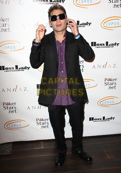 "COREY FELDMAN. Lupus LA Raises Awareness with ""Get Lucky for Lupus"" held At Andaz Hotel, West Hollywood, California, USA..February 25th, 2010.full length black trousers suit jacket purple shirt sunglasses shades hand mouth open funny .CAP/ADM/KB.©Kevan Brooks/AdMedia/Capital Pictures."