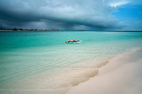Man diving in water with storm clouds over ocean at Turks and Caicos.