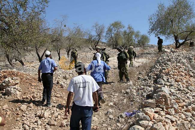 Israeli soldiers prevent Palestinian farmers (bottom) and Israeli settlers from fighting after a farmer was wounded by Israeli settlers from the Yizhar settlement who were attack the Palestinian farmers , on Sept. 20, 2010 in the West Bank village of Burin . Photo by Wagdi Eshtayah
