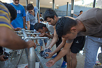 Illegal migrants drink water and wash themselves in a transit zone at the main railway station Keleti in Budapest, Hungary on August 30, 2015. ATTILA VOLGYI