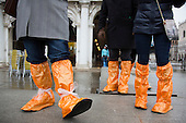 Orange plastic boots. As the annual Carnival celebrations get underway in Venice, high water (acqua alta) floods many parts of the city. Many tourists have been caught out by the high water and had to buy reinforced plastic boots in bright colours - which are worn over normal shoes - to keep dry. Better weather is forecast for the carnival celebrations in St Mark's Square this weekend.