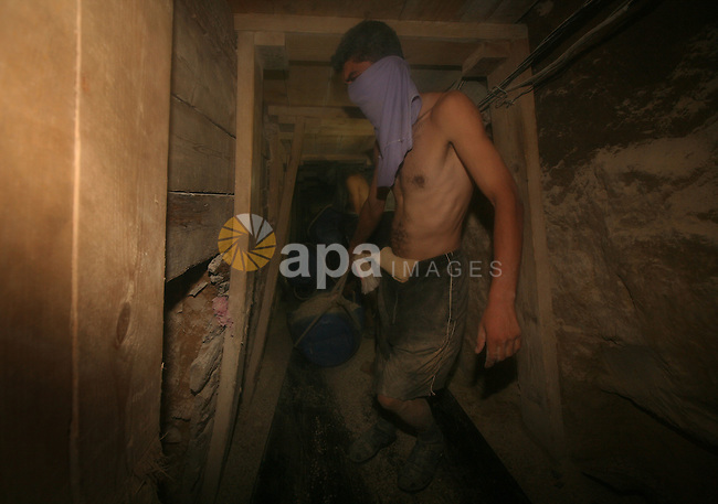 Palestinian men smuggle gravels into the Gaza Strip through a tunnel under the Egypt-Gaza border in Rafah on Oct. 16, 2011. Israel released a list of 477 Palestinian prisoners to be released next week as part of the deal to secure Gilad Shalit's freedom, many of whom were involved in bloody militant attacks, as Israel stopped allowing to enter the construction materials into Gaza Strip since Shalit's capture. Photo by Mahmud Nassar