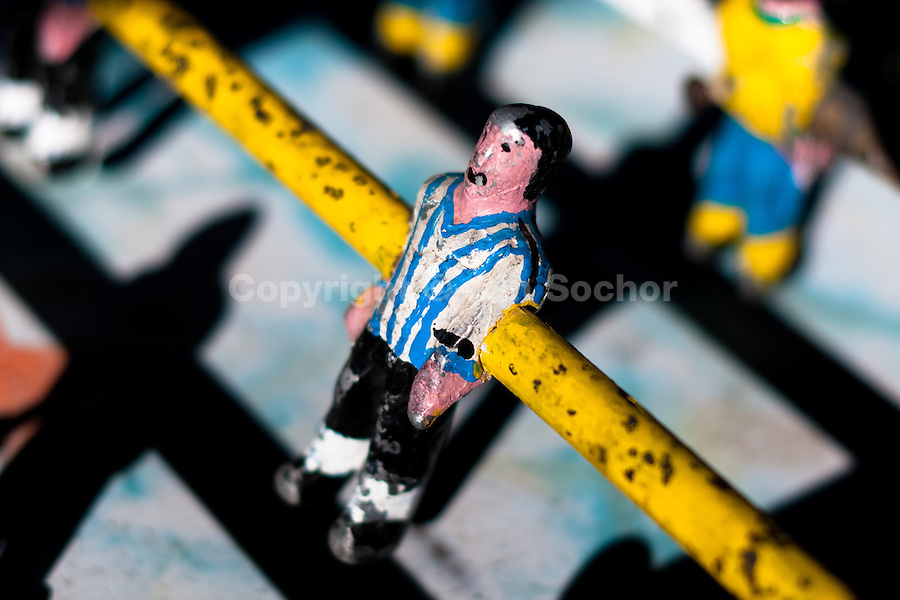 A table football player figure, with a painted white and blue shirt, is seen inside the table football box on the street of Otavalo, Ecuador, 28 June 2010. Table football, also known as futbolin in Latin America, is a widely popular table-top game in Ecuador. During the annual fairs, the rusty old outdoor-designed tables, fully ocuppied by excited children, may be found on all public places, particularly on the squares and in the parks. Human players use figures mounted on rotating bars to kick the small plastic ball into the opposing goal. Each team of 1 or 2 human players controls 4 rows on its side of the table. The game ends when one team scores a predetermined number of goals. In 2002, the International Table Soccer Federation (ITSF) was established to promote the sport of table football.