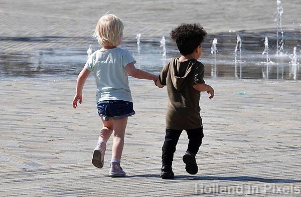 Nederland - Leeuwarden -  april 2018. Twee kinderen rennen hand in hand naar een fontein.   Foto mag niet in negatieve context gepubliceerd worden.   Foto Berlinda van Dam / Hollandse Hoogte