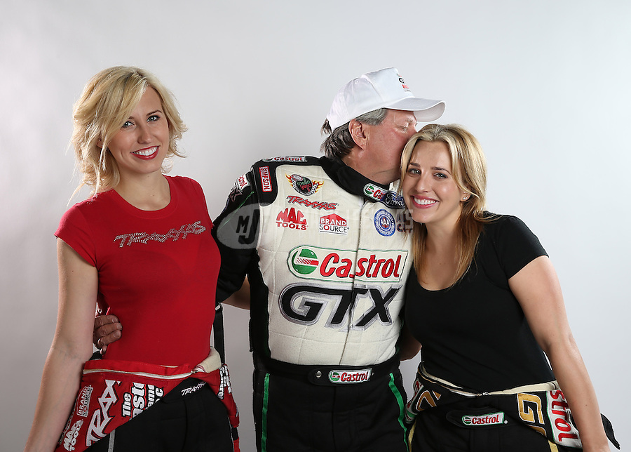 Feb. 22, 2013; Chandler, AZ, USA; NHRA funny car driver Courtney Force (left) with father John Force (center) and sister Brittany Force pose for a portrait prior to qualifying for the Arizona Nationals at Firebird International Raceway. Mandatory Credit: Mark J. Rebilas-