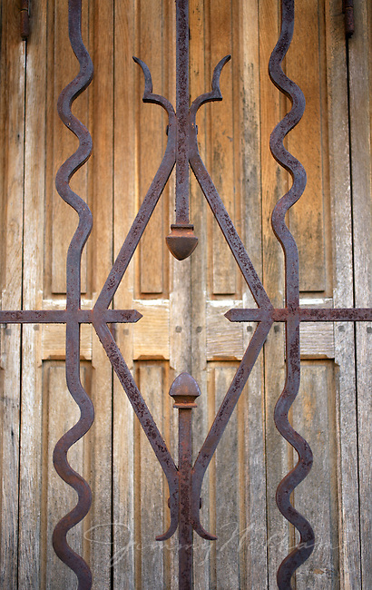 An old iron gate sits in front of a wooden door at a home in Didier, France