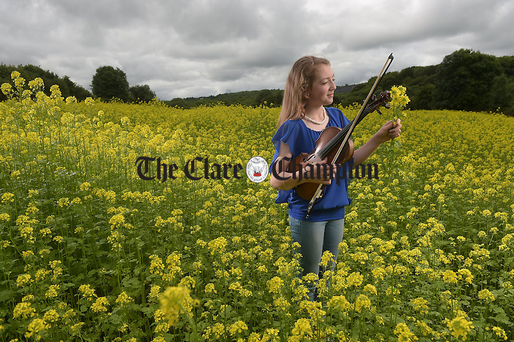 The Hills Are Alive With The Sound Of Music....Musician and Fleadh competitor Eve O Connor of Ruan in field of Linseed bird cover,  grown as part of the GLAS scheme at Drumcaurin, Ennis. The countdown is now on for the All-Ireland Fleadh which takes place from 14th to 22nd August. Photograph by John Kelly.