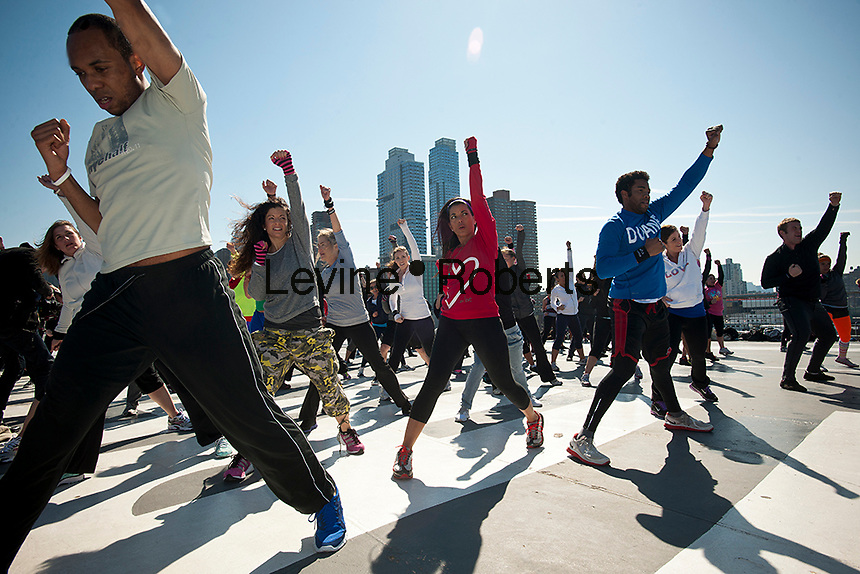 "Exercisers participate in an ""IntenSati"" exercise class on the flight deck of the Intrepid Sea, Air and Space Museum in New York on Sunday, March 11, 2012 during the museum's Health & Fitness Day promotion. IntenSati is a combination of interval training, martial arts, dance and yoga.  (© Richard B. Levine)"