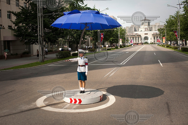 A traffic controller gestures to traffic under an umbrella in the middle of a road in Pyongyang.