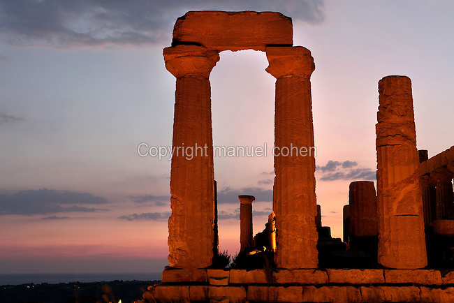Detail of columns, Temple of Juno or Hera Lacinia, c.450 BC, Agrigento, Sicily, Italy,  pictured on September 11, 2009, floodlit against a dramatic evening sky. This temple was built on an artificial spur. Standing on a high rectangular platform above four steps its 34 fluted columns consist of four tamburi or drums and are each 6.32 meters high. Today, 30 columns are standing but only sixteen with their capitals. After being damaged in the fire of 406 BC it was restored in Roman times, and again in 1787 by the Prince of Torremuzza. The Valley of the Temples is a UNESCO World Heritage Site. Picture by Manuel Cohen.