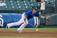 Round Rock Express third baseman Jason Donald (5) dives towards a grounder during the Pacific Coast League baseball game against the Omaha Storm Chasers on June 1, 2014 at the Dell Diamond in Round Rock, Texas. The Express defeated the Storm Chasers 11-4. (Andrew Woolley/Four Seam Images)
