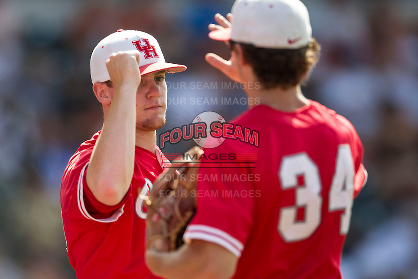 Houston Cougars pitcher Bubba Maxwell (28) greets teammate Kyle Survance (34) during the NCAA baseball game against the Texas Longhorns on June 6, 2014 at UFCU Disch–Falk Field in Austin, Texas. The Longhorns defeated the Cougars 4-2 in Game 1 of the NCAA Super Regional. (Andrew Woolley/Four Seam Images)
