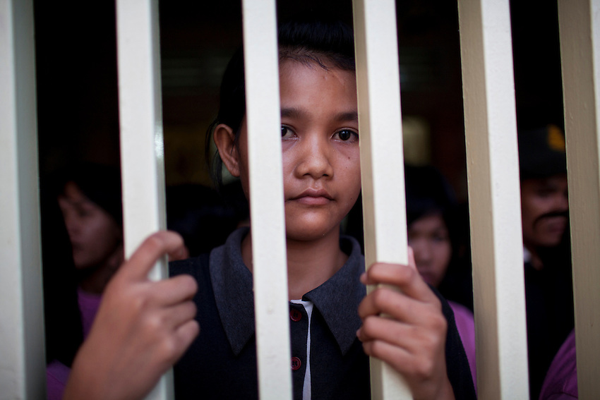 Soeung Soday, an 18-year-old domestic migrant worker, looks through the bars of a heavy metal gate that prevents recruits from leaving an SKMM Investment Group training centre in Russey Keo district, Phnom Penh, October 19, 2011. The recruitment firm, which sends Cambodian maids to Malaysia for placement, was raided the following day. More than 70 women who claim they were being held against their will, including a number of underage girls, were freed from the company's three training centers in Phnom Penh. According to Cambodian law, domestic workers must be at least 21 years of age to travel to Malaysia to work as maids, however some of the recruits who were as young as 15 and 16 and stated that the company had falsified travel documents to bypass the rules.