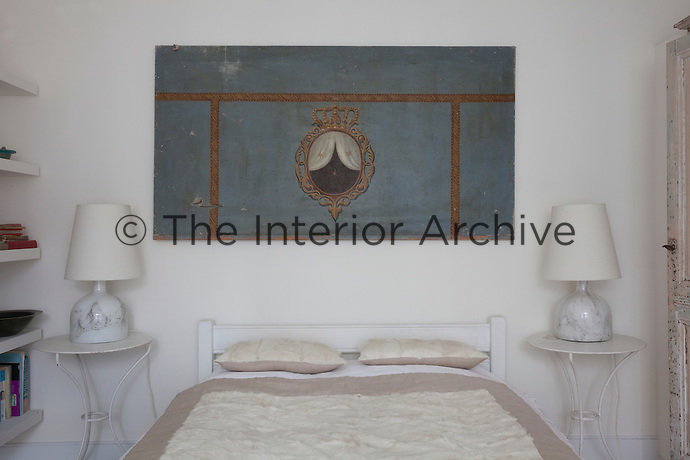 What appears to be an antique piece of stage set, or painted panelling, hangs above the bed in the guest bedroom