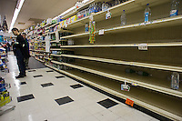 """Shelves stripped bare of bottled water by customers stocking up for Hurricane Sandy in a Gristede's supermarket in the Chelsea neighborhood of New York on Sunday, October 28, 2012. In advance of the arrival of Hurricane Sandy New York will down the subways at 7 PM on Sunday and evacuate low lying """"Zone A"""" areas including Battery Park City. In addition the schools will be closed on Monday. (© Richard B. Levine)"""