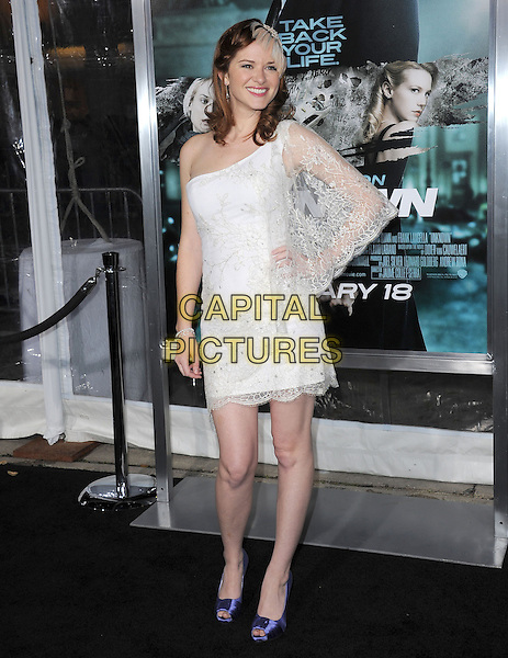 SARAH DREW.Premiere of Unknown held at The Regency Village Theatre in Westwood, California, USA..February 16th, 2011      .full length dress one sleeve hand on hip white one shoulder feather hair hat purple peep toe shoes smiling.CAP/RKE/DVS.©DVS/RockinExposures/Capital Pictures.