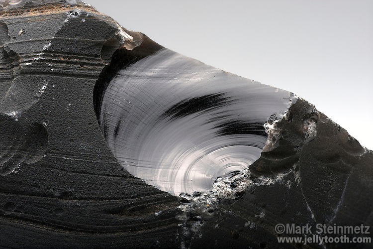 Close-up view of a conchoidal fracture in obsidian. Conchoidal fracturing is often said to resemble a clamshell, and is characteristic mineral property of pure silicates such as obsidian and window glass.