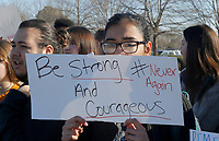 NWA Democrat-Gazette/DAVID GOTTSCHALK Mandeep Kaur, a senior at Bentonville High School, holds a sign Wednesday, March 14, 2018, before a a 17 minute silent observance for the shooting victims  Marjory Stoneman Douglas High School in Parkland, Florida. About 400 students from the school participated in the silence and a series of chants and speeches as they lined S.E. J Street in Bentonville.
