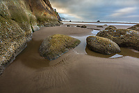 Hug Point State Park, Oregon: Sunrise at low tide with exposed rocks and cliff face