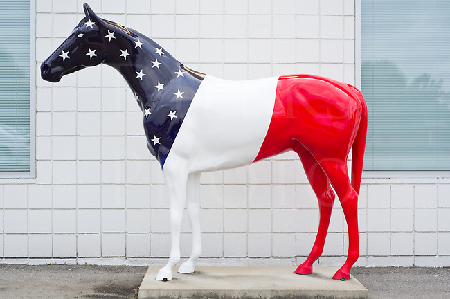 Patriotic horse statue painted in red, white, and blue with stars in an American flag theme, full body side view.